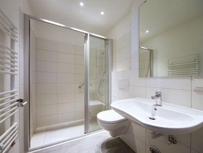 weißes Bad mit Waschbecken und Dusche