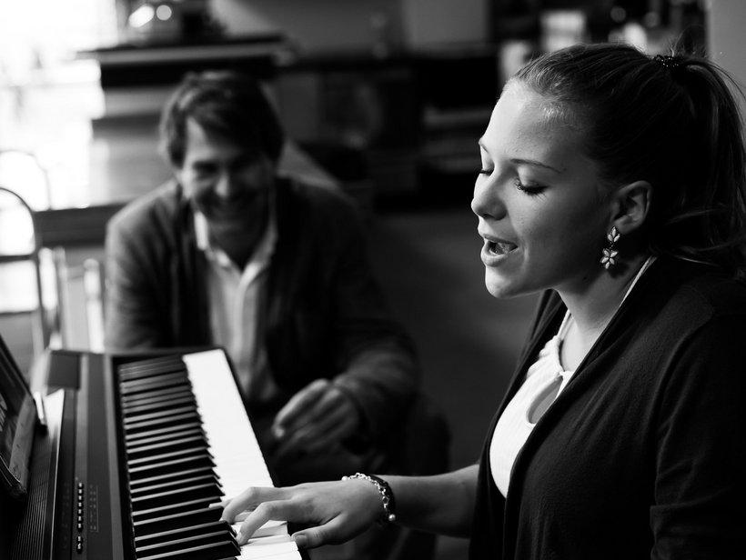 Frau spielt Klavier und singt