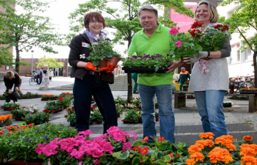 Floristin berät zwei Kunden, alle haben Pflanzen in der Hand